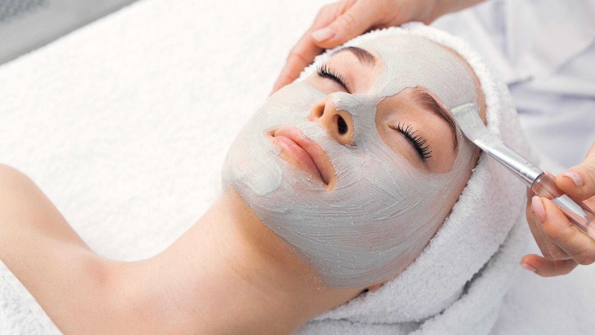 Patientin erhält ein Peeling im Gesicht.
