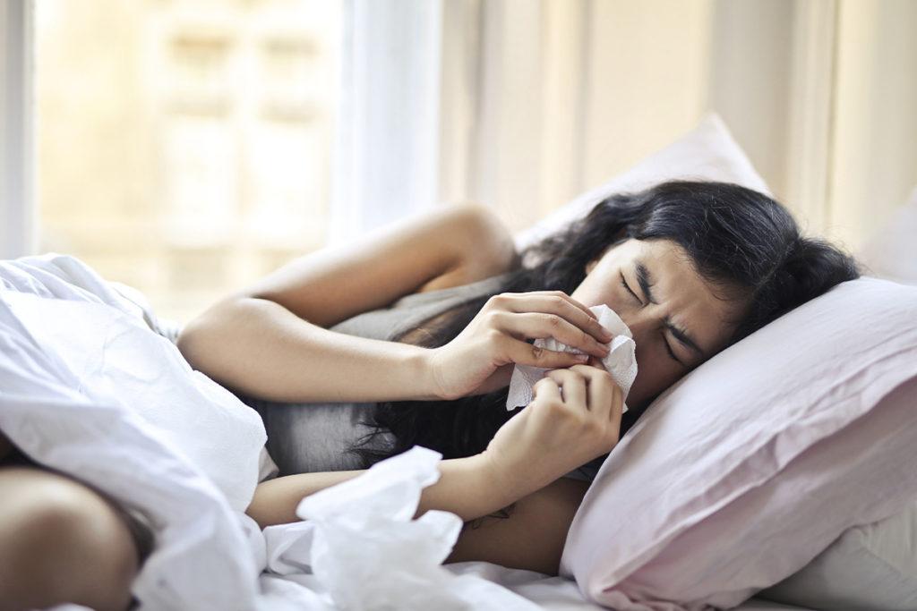 Frau liegt mit Heuschnupfen im Bett