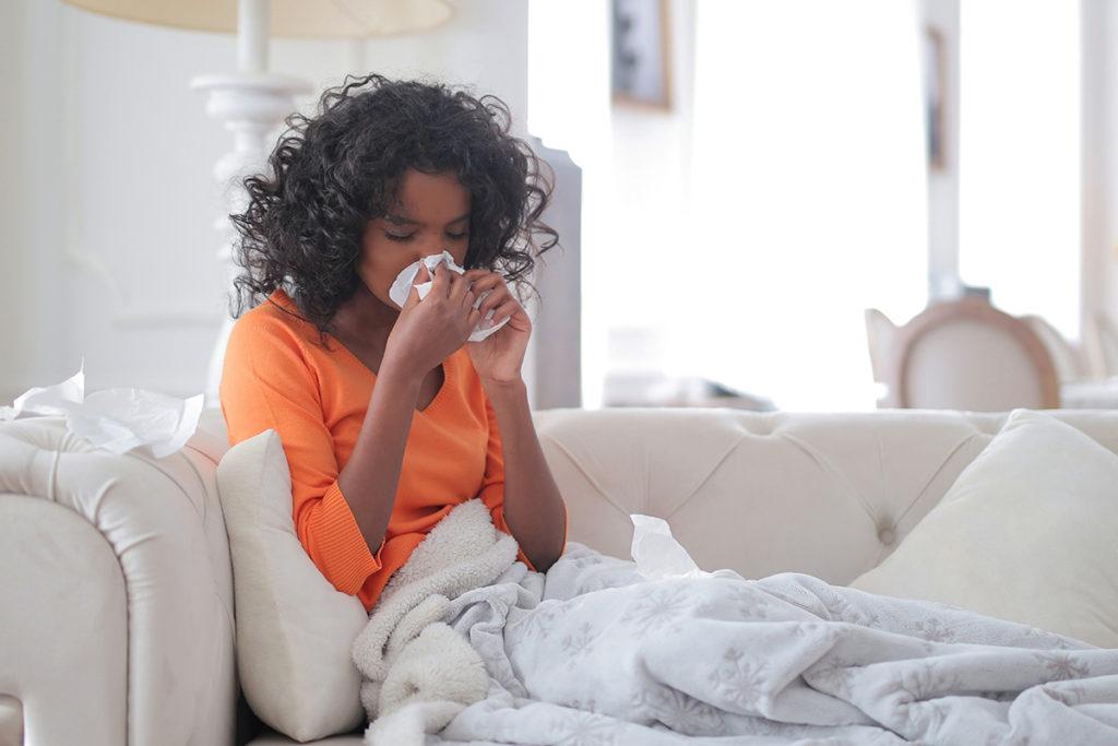Junge Frau leidet an einer Allergie und sitzt auf dem Sofa.