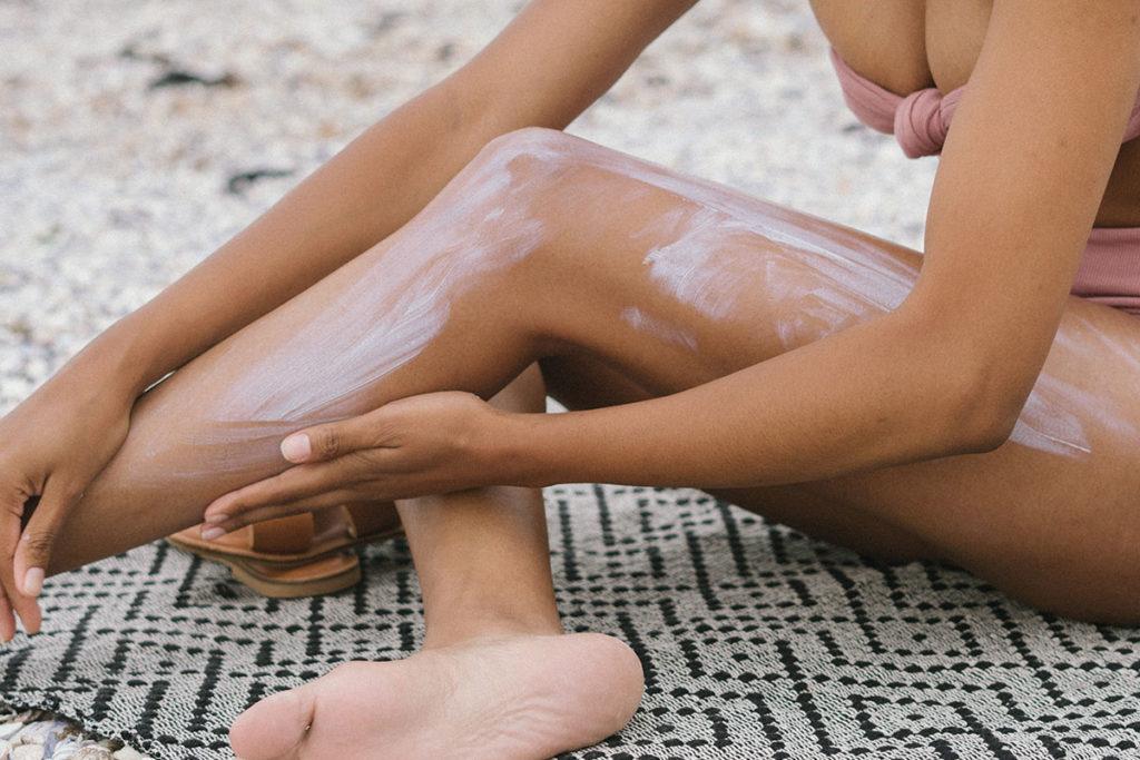 Frau sitzt auf einem Handtuch und trägt Sonnenschutzmittel auf
